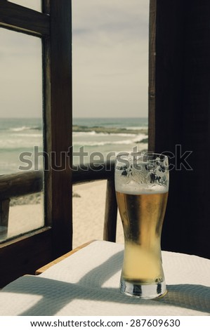 Cold beer on cafe terrace with the view on the ocean beach through the opened window. Algarve, Portugal. A game of light an shadow. Aged toned photo. - stock photo