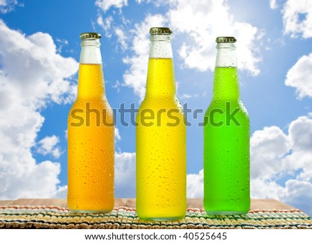 Cold beverages in glass bottles on wooden table top with nice blue sky in the background