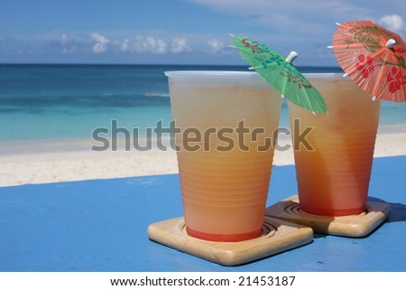 Cold beverages on coasters at beach front of island resort