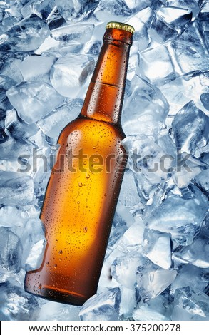 Cold bottle of beer in the ice cubes. There is condensated moisture over glass. - stock photo