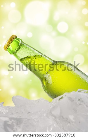 Cold bottle with dew and fresh lager on the ice cube, shot with bokeh background - stock photo