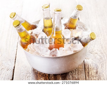 cold bottles of beer in bucket with ice on wooden table - stock photo