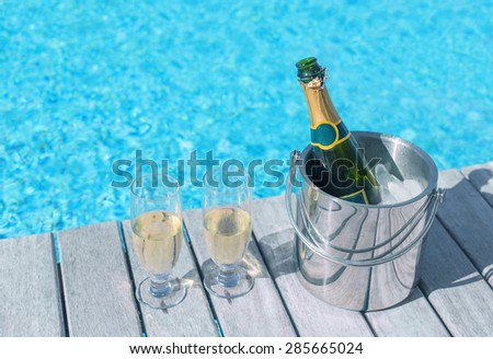 Cold champagne bottle in ice bucket and two glasses of champagne on the deck by the swimming pool - stock photo