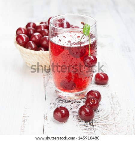 Cold cherries drink with fresh cherry on white wooden table - stock photo