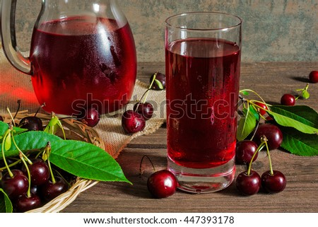 cold cherry juice in a glass and pitcher on wooden table with ripe berries in wicker basket - stock photo