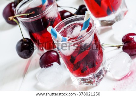 Cold cherry juice with ice on a white wooden background, selective focus - stock photo