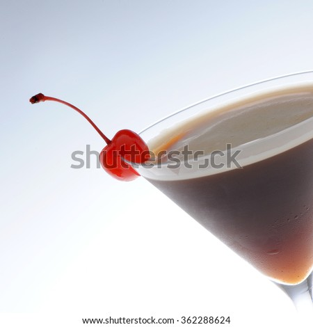 Cold cocktail with a cherry in martini glass isolated - stock photo