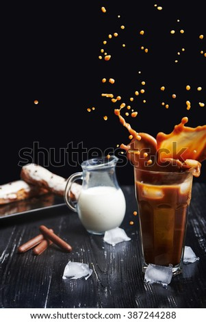 Cold coffee drink with ice and splashes in dark wooden background with eclair and chocolate sticks. Vertical shot. Dark photo. - stock photo