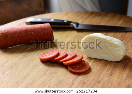 Cold cuts/Sliced pepperoni on cutting board with piece of mozzarella cheese & knife in soft light - stock photo