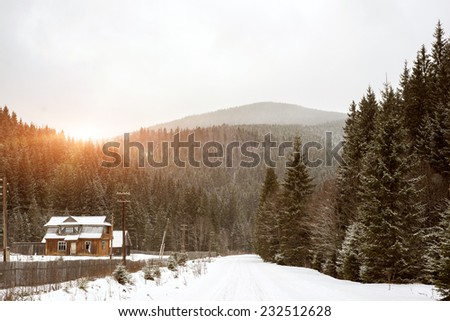 Cold day up in the mountains with a road that people have gone over. Scene is covered in snow on the sunset. - stock photo