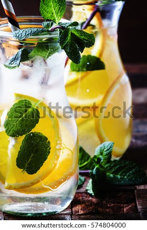 Cold drink with orange, mint and ice,  vintage wooden background, selective focus