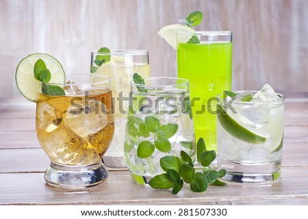 Cold drinks with fruits and mint on wood background - stock photo