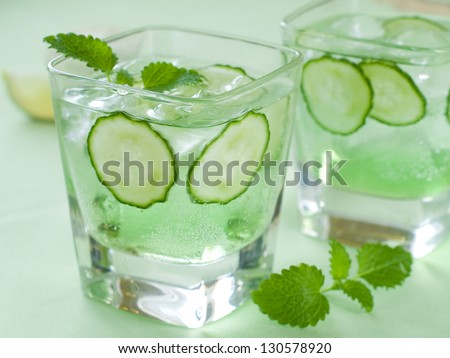 Cold fresh lemonade with cucumber and ice, selective focus - stock photo
