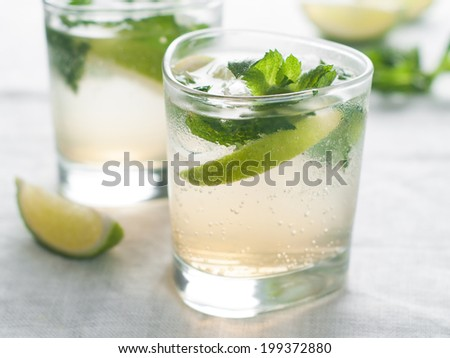Cold fresh lemonade with lime and mint, selective focus  - stock photo