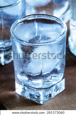 Cold fresh water with ice in a heart shape in the misted glasses, selective focus - stock photo