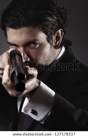 Cold gaze from gangster aiming with a shotgun. Grey backdrop portrait