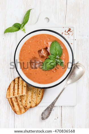 Cold gazpacho tomato soup in bowl with ice, hot pepper and basil served with toasted bread on ceramic board over white painted wooden background, top view, vertical composition