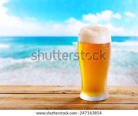 cold glass of beer on wooden table over sea - stock photo