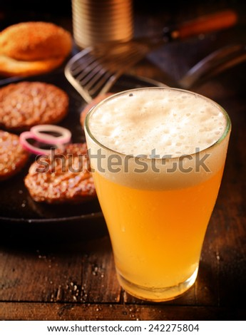 Cold glass of frothy beer standing alongside a pan of grilled beef burger patties in a pub or restaurant , high angle with focus to the frothy head of the lager - stock photo