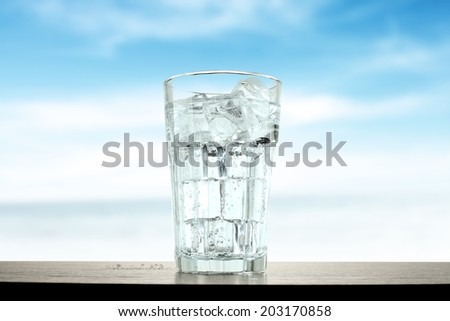 cold glass of ice water and blue sky  - stock photo