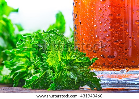 Cold glass of iced tea with mint on wooden table top.  - stock photo
