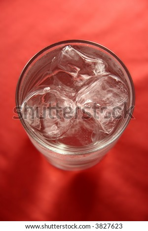 cold glass of water and ice rocks on bright red background. top view, soft focus. - stock photo