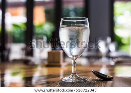Cold Glass Of Water On Wooden Table At Restaurant.