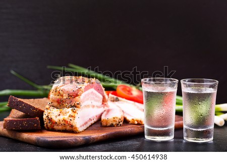 cold glasses of vodka with snack on dark background - stock photo