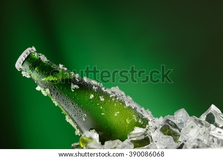 Cold green bottle of beer with water droplets and ice cubes over green background - stock photo