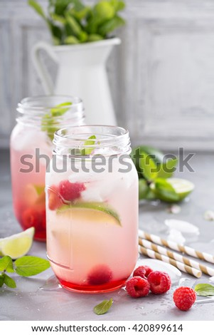 Cold green iced tea in mason jars with lime and raspberry - stock photo