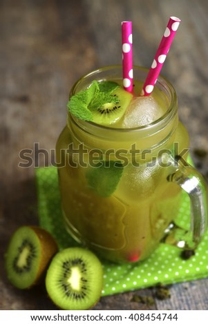 Cold green tea with kiwi and mint in a mason jar on rustic wooden table.