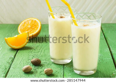 Cold homemade milkshake with ice cream, orange juice and nutmeg in a glass with cocktail straws, slices of orange, nutmeg on a green wooden table. Selective focus