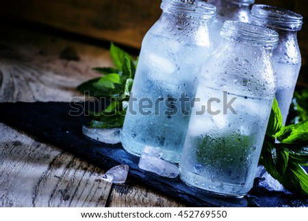 Cold isotonic solution for sports nutrition in glass bottles, dark background, selective focus - stock photo
