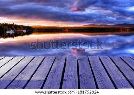 Cold lake with clouds wooden dock - stock photo