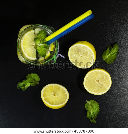 Cold lemonade in bottles with lemons on a black background. Top view - stock photo
