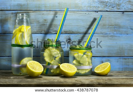Cold lemonade in bottles with lemons on a blue wooden background. - stock photo