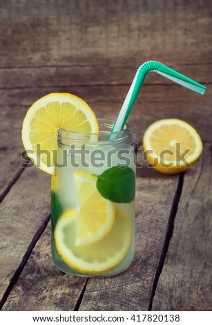 Cold lemonade with ice. Detox cocktail. Refreshing homemade lemon and mint cocktail over old vintage wooden table. Detox fruit infused flavored water - stock photo