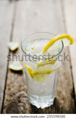 cold lemonade with ice on a wooden table - stock photo