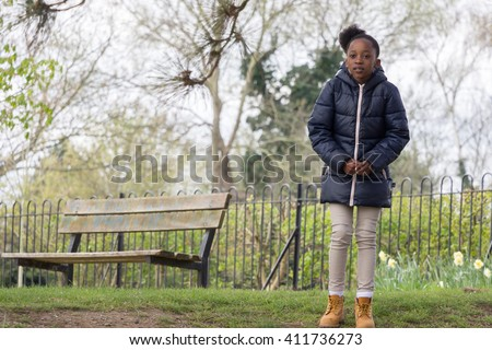 Cold little girl standing in the park