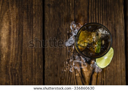 Cold Longdrink (Cuba Libre) with brown rum and fresh lime on rustic wooden background - stock photo