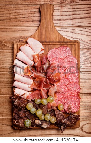Cold meat plate, slices prosciutto, ham,beef jerky, sausage, salami with grapes and spice on wooden cutting board - stock photo