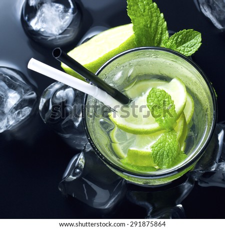 cold Mojito cocktail with fresh lime, mint and ice on black table - stock photo