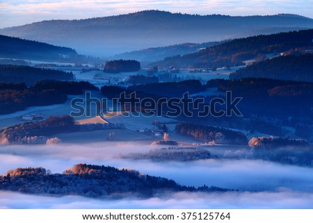 Cold morning in Sumava National park, hills and villages in the fog and rime, misty view on czech landscape, blue winter scene, Tristolicnik, Czech Republic