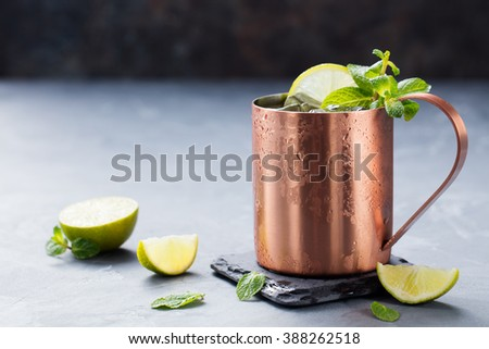 Cold Moscow Mules cocktail with ginger beer, vodka, lime Grey stone background Copy space - stock photo