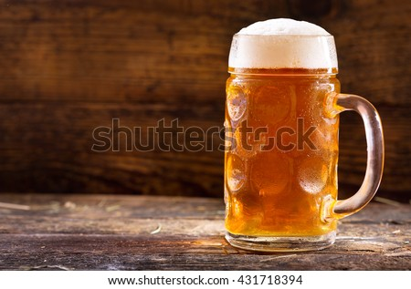 cold mug of beer on wooden table - stock photo