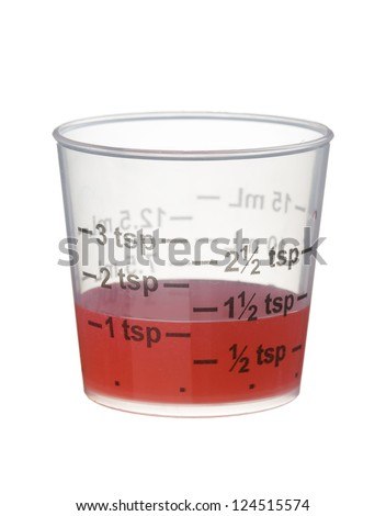 Cold or cough syrup medicine in a measuring cup isolated on white background