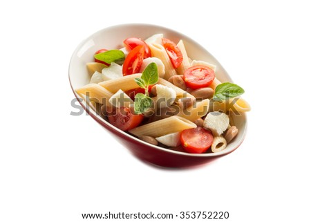 cold pasta salad with slice tomatoes mozzarella and beans  - stock photo