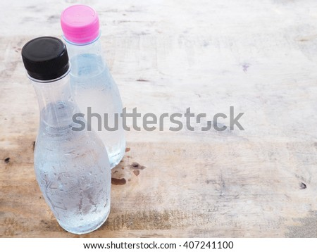 Cold plastic bottle water on the wooden table - stock photo