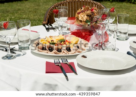 Cold plate with cheese and ham and fruit. Decorated table white and red in the garden