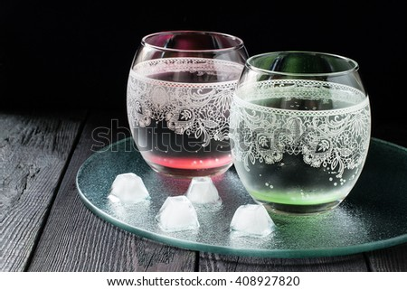 Cold pure mineral water in a beautiful glass with ornaments on the dark background  - stock photo